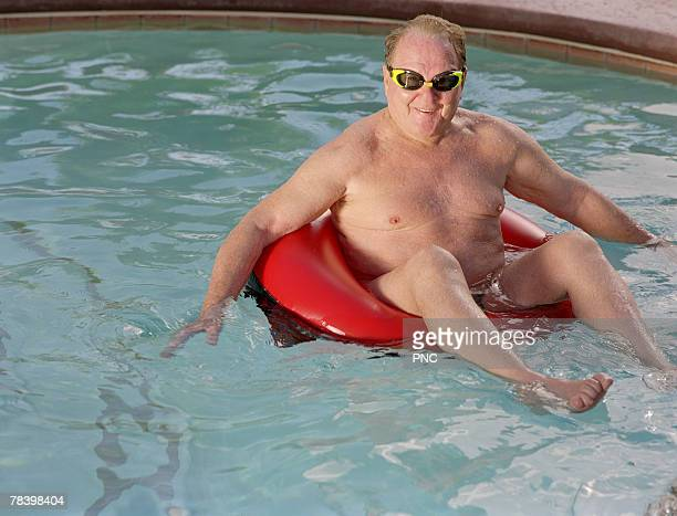 Funny man floating in swimming pool