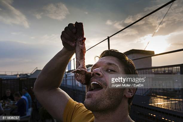 Funny man holding a piece of raw meat on mouth