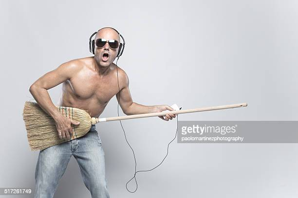 Funny man playing air guitar with broom