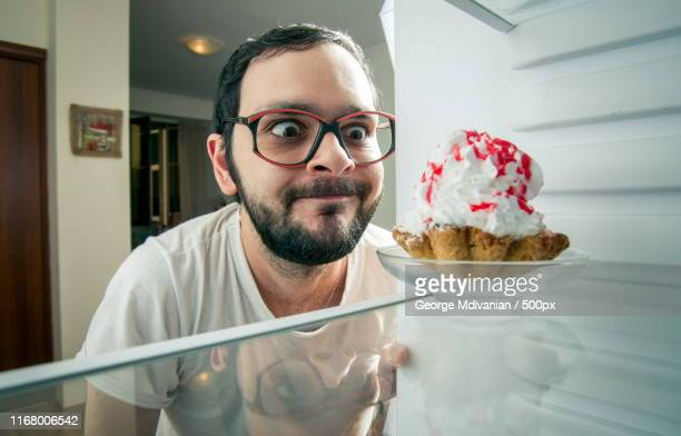 funny man sees the sweet cake in the fridge - frigo humour photos et images de collection