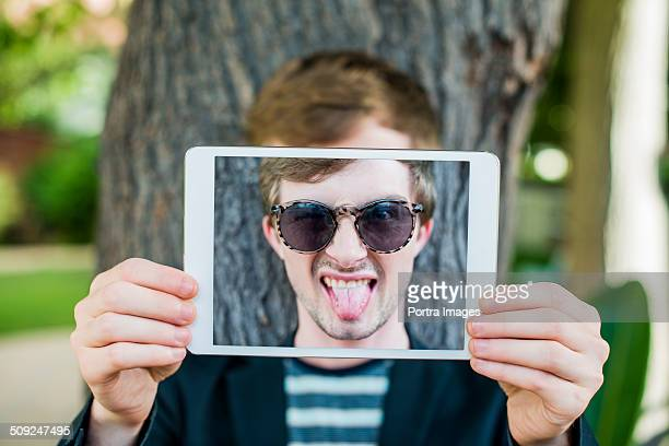 Funny man taking self portrait on digital tablet