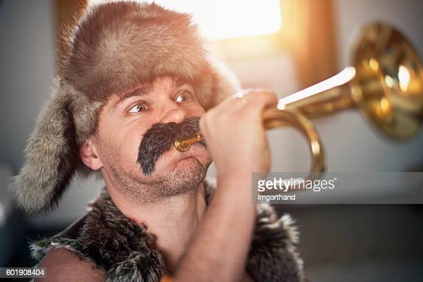 Funny man with big moustache playing trumpet