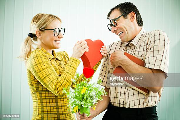 Funny nerds holding Valentine presents.