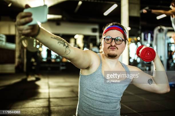funny nerdy atlet visar upp när du tar en selfie i ett gym. - humor bildbanksfoton och bilder