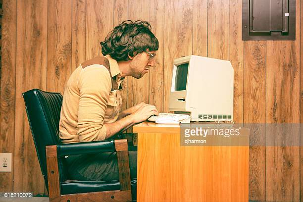 funny nerdy man looking intensely at vintage computer - typen stockfoto's en -beelden