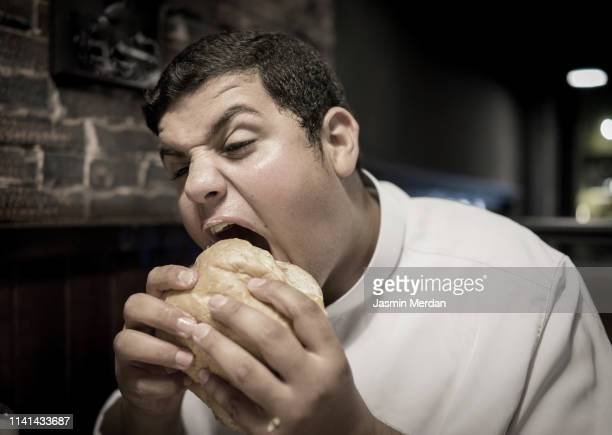 funny overweighted boy eating burger - chubby arab photos et images de collection