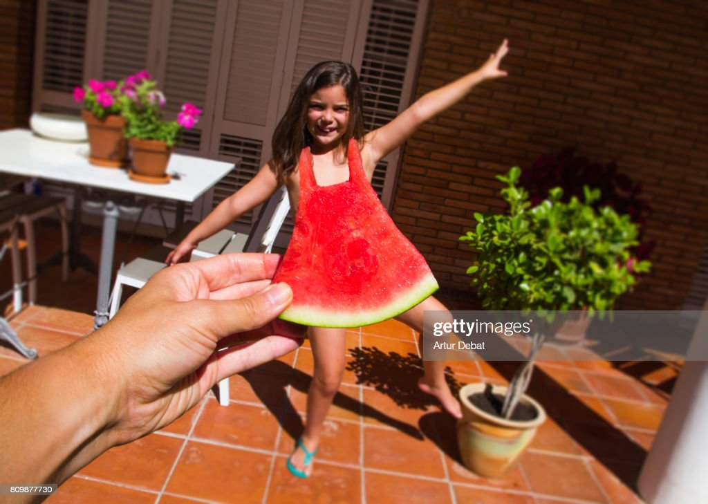 Funny picture of a watermelon dress challenge taken from personal point of view fitting a size of watermelon with a little girl, playing with perspective. : Stock Photo