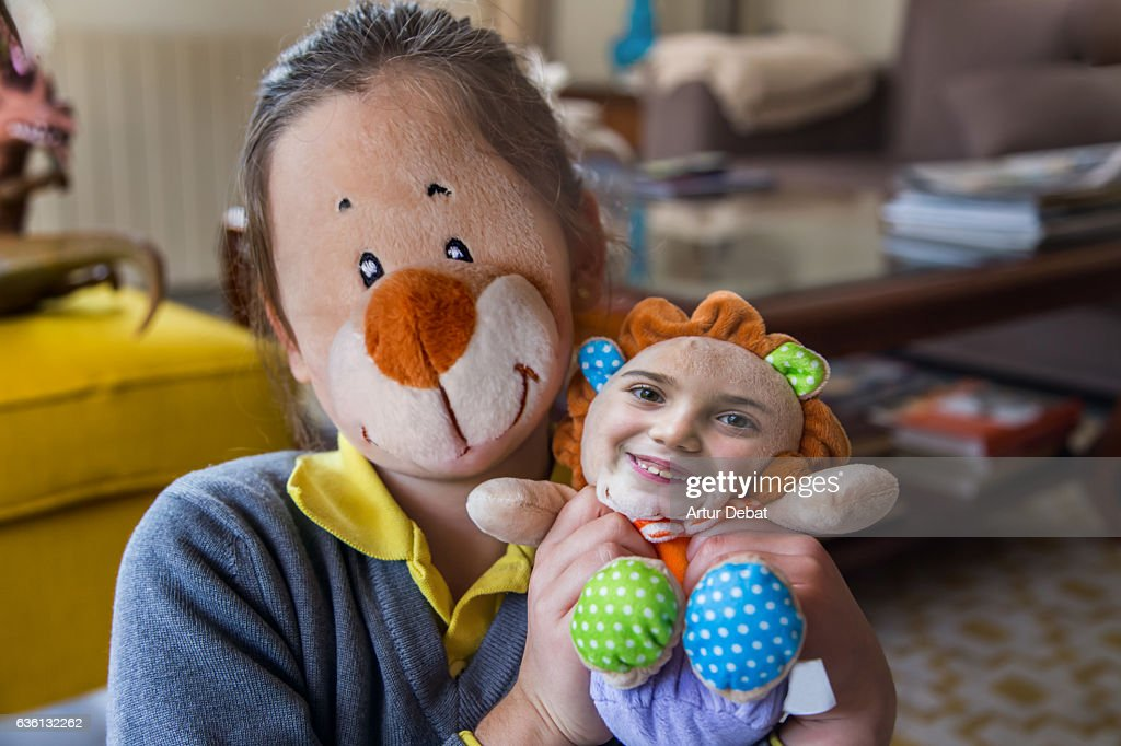 Funny picture swapping faces using smartphone application with little girl and her teddy toy. : Stock Photo