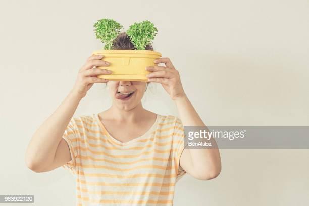 drôle de portrait fille tenant des plantes devant son visage après un rempotage réussi - jardinier humour photos et images de collection