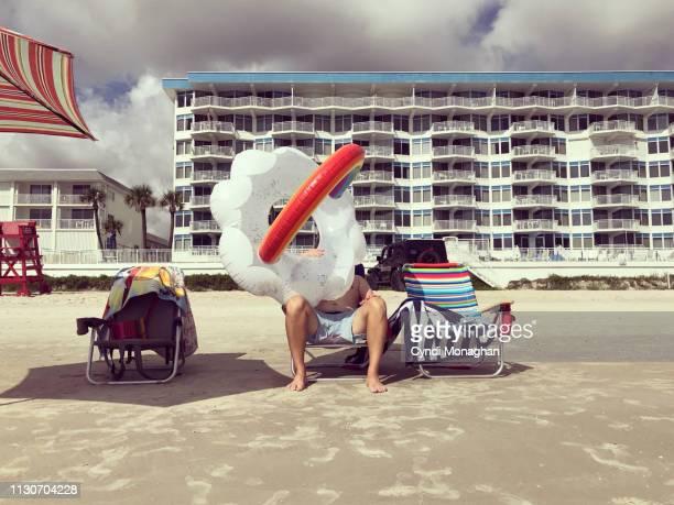 funny portrait of a man blowing up a rainbow cloud inner tube at the beach - form ändern stock-fotos und bilder