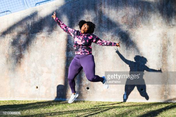 funny portrait of a young black curvy woman during a training session - plus size model stock pictures, royalty-free photos & images