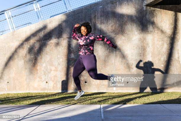 funny portrait of a young black curvy woman during a training session - funny fat women stock pictures, royalty-free photos & images