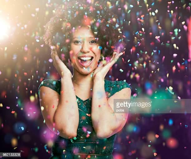 roliga porträtt av en ung kvinna med konfetti flyger runt henne - flying solo after party bildbanksfoton och bilder
