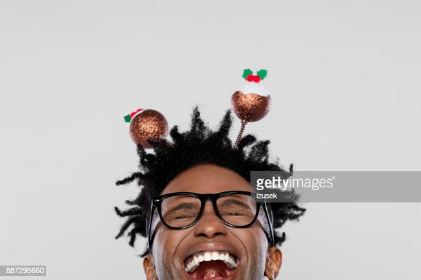 Funny portrait of excited nerdy man wearing christmas headband