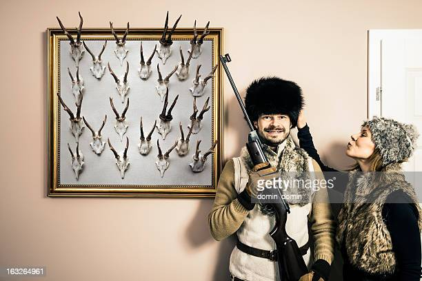 Funny portrait of hunter with shotgun and his wife, antlers
