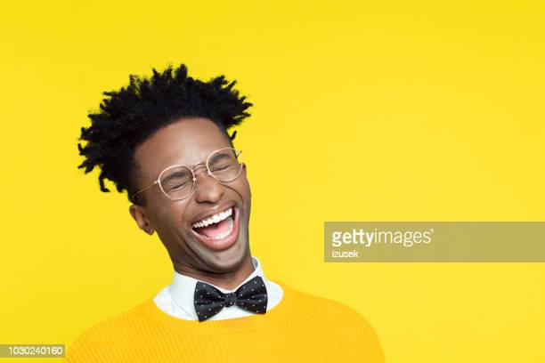 funny portrait of nerdy young man laughing with eyes closed - comedian stock pictures, royalty-free photos & images