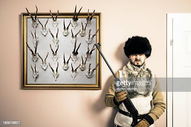 Funny portrait of serious hunter man with shotgun and antlers