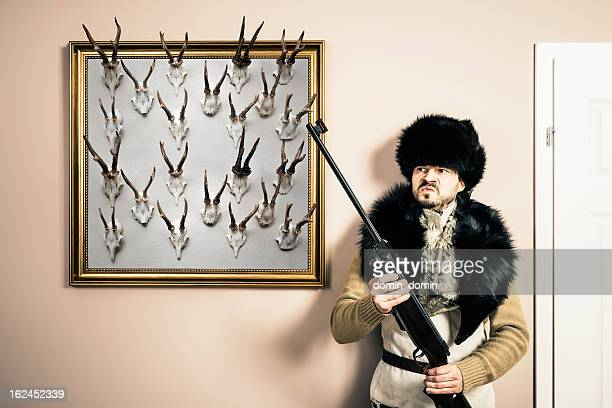 Funny portrait of serious hunter with shotgun and antlers, studio