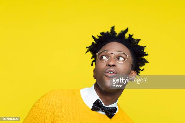 funny portrait of surprised nerdy young man looking up - bold man stock photos and pictures