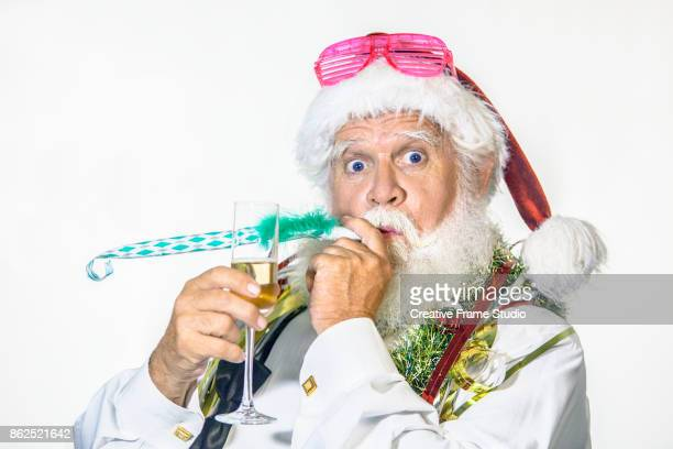 Funny Santa Claus celebrating with a glass of champagne and blowing a party blowout