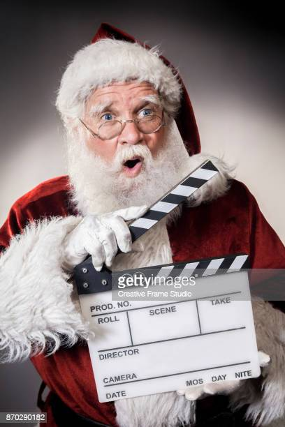 funny santa claus holding a film clapperboard - spotlight film stock photos and pictures