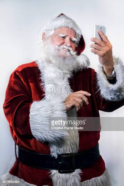 Funny Santa Claus taking a selfie with a smart phone
