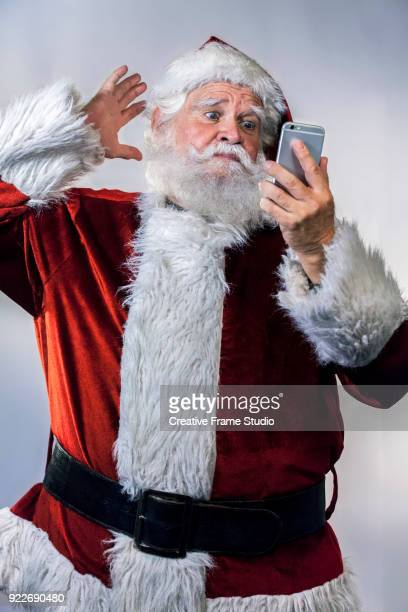 Funny Santa Claus taking a selfie with a smartphone