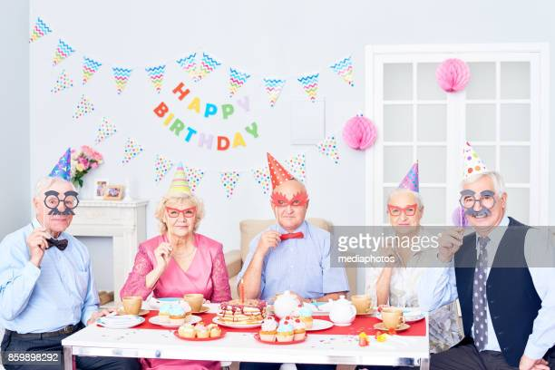 Funny seniors in masks at birthday party
