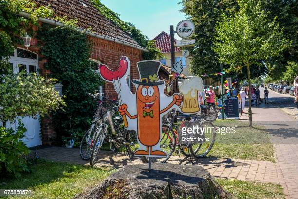 A funny signboard with a sausage dressed in bowtie and top hat advertises grilled sausages and beer outside Juhl's restaurant in the village of...