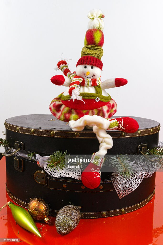 Funny snowman sits on vintage brouwn coffer with white christmas : Stockfoto