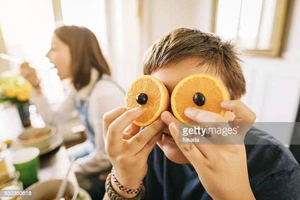 Drôle jeune garçon avec des fruits sur les yeux