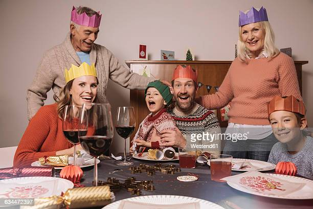 Funny three-generation family portrait with paper crowns during Christmas dinner