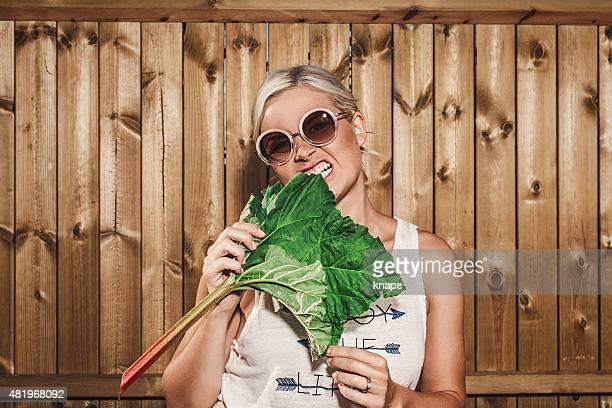 Lustiger wierd Frau mit Rhabarber im Freien im Sommer