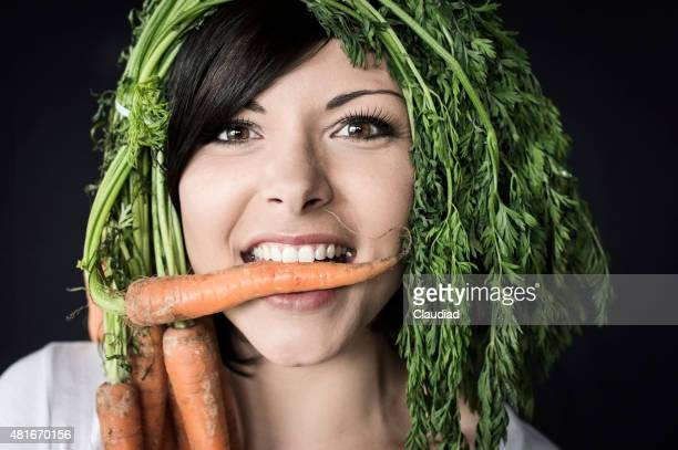 Funny woman eating carrot