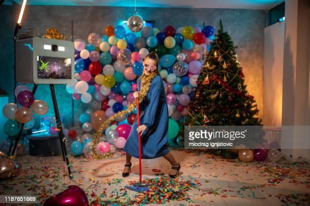 funny woman having good time while cleaning after party - christmas after party stock pictures, royalty-free photos & images