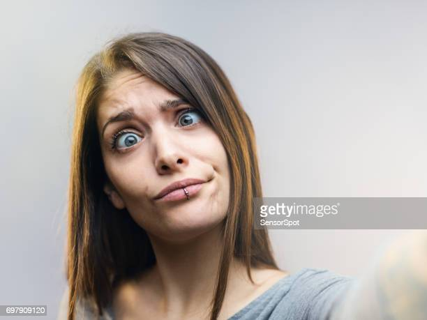 funny woman posing for a selfie against gray background. - cross eyed stock pictures, royalty-free photos & images