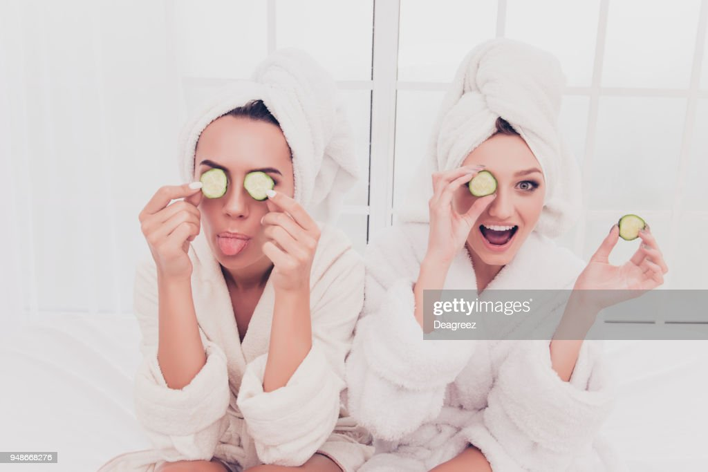 Funny young girls in bathrobes making mask with cucumber and having fun : Stock Photo