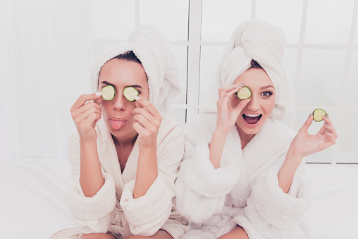 Funny young girls in bathrobes making mask with cucumber and having fun 948668276