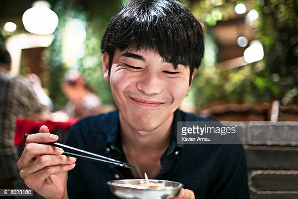 Funny young japanese man eating using chopsticks