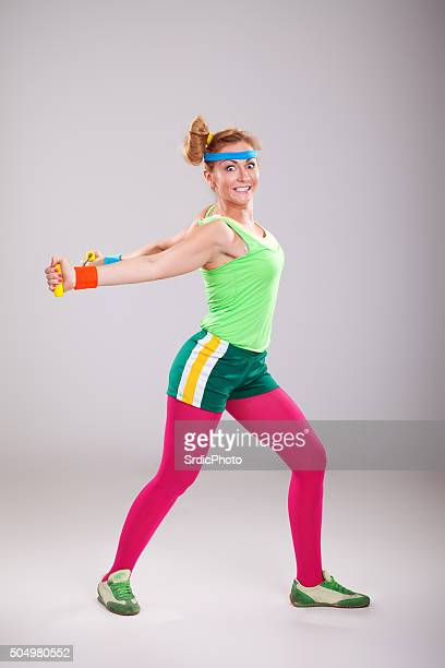 Funny young woman doing stretching exercises with resistance band