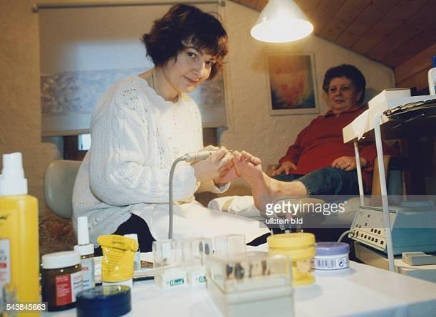 Fußpflegerin Maria VolzHimbert bearbeitet mit einem elektrischen Gerät die Fußnägel einer älteren Patientin die ihr Bein auf einen Hocker gelegt hat...