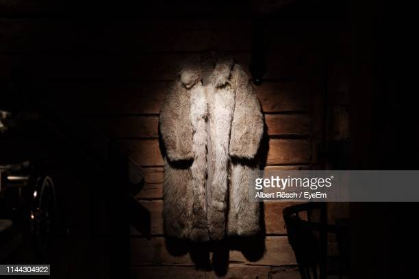 fur coat against wall at home - fur coat stock pictures, royalty-free photos & images