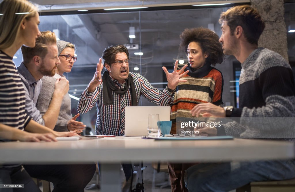 Furious boss shouting at his team on a meeting in the office. : Stock Photo