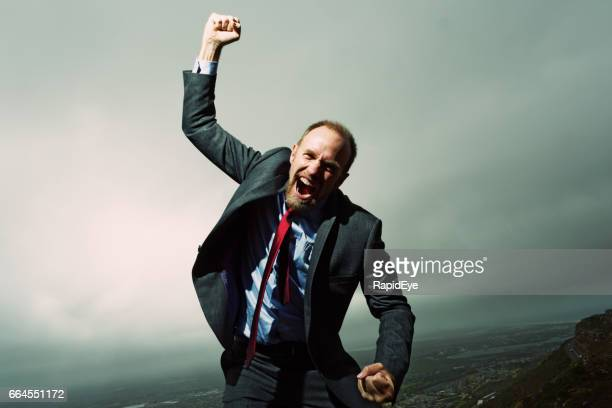 Furious businessman rages at fate against a stormy sky