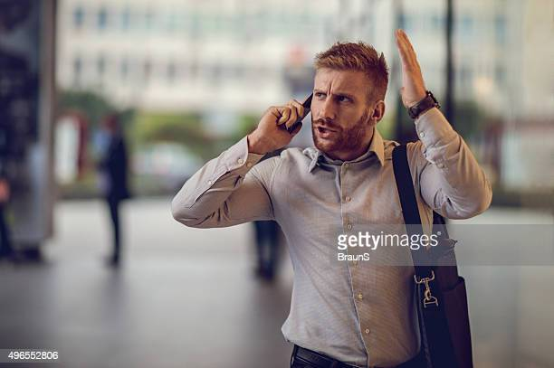 Furious businessman talking to someone over smart phone.