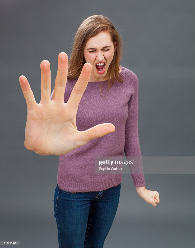 furious girl having tantrum, shouting in showing large hand forward : Photo