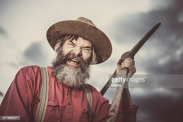 furious gold miner with pickaxe - gold rush stock photos and pictures