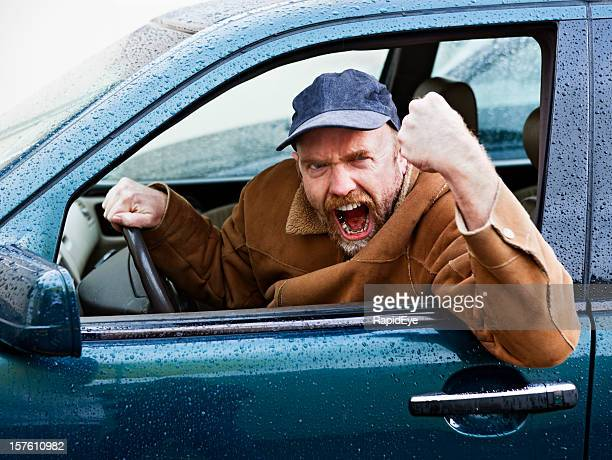Furious male driver shakes his fist out of car window