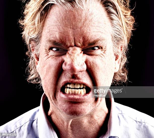 furious middle-aged man snarls, frowning and grimacing - ugly teeth stock photos and pictures