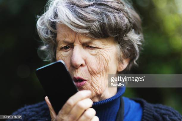 Furious or frustrated senior woman shouts into mobile phone